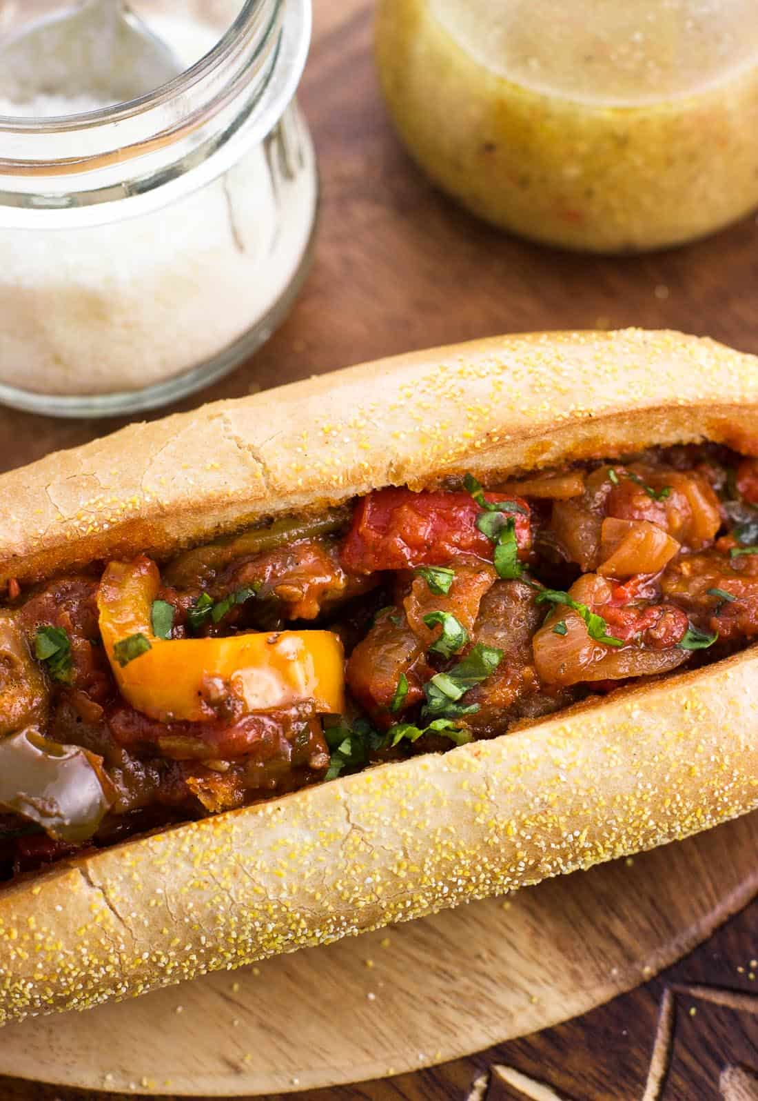 A close up shot of an Italian sausage and peppers sandwich