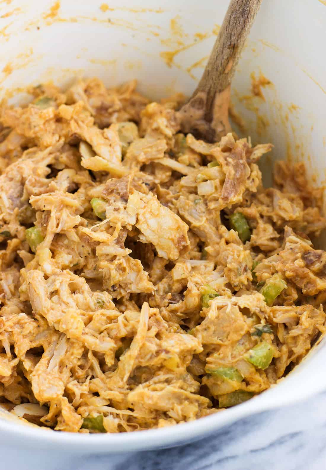 Mixed together buffalo chicken salad in a bowl with a wooden spoon