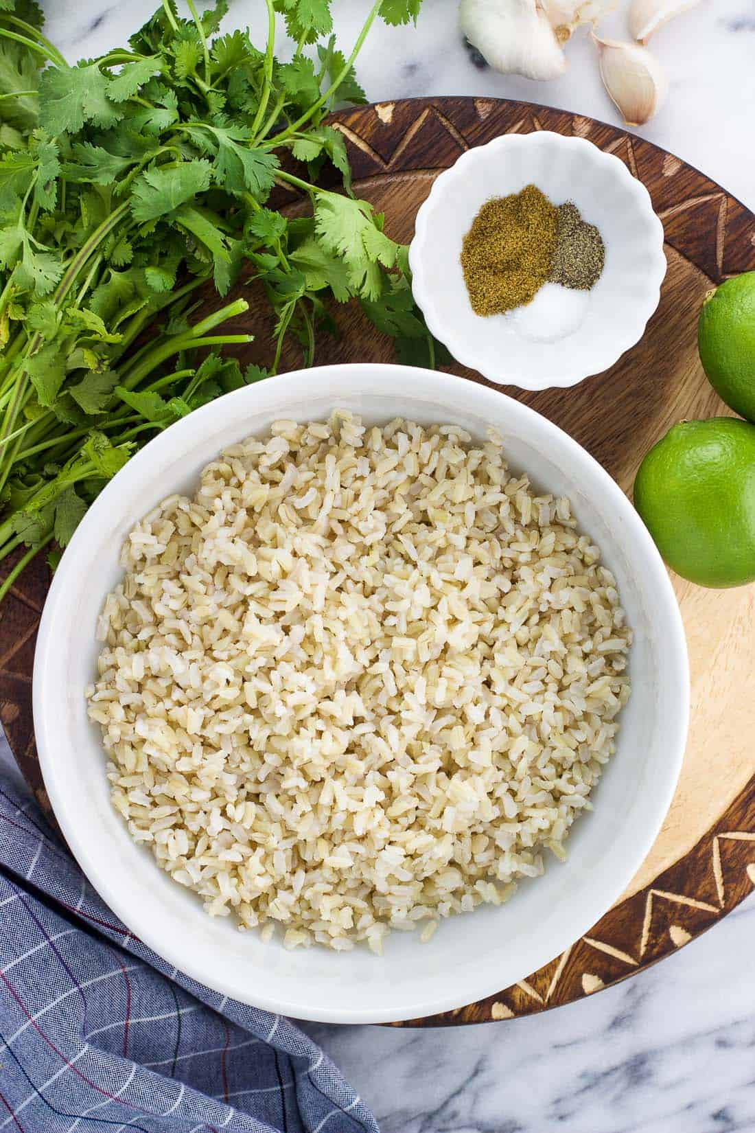 An overhead shot of the ingredients, including cooked rice, a bunch of cilantro, limes, and spices