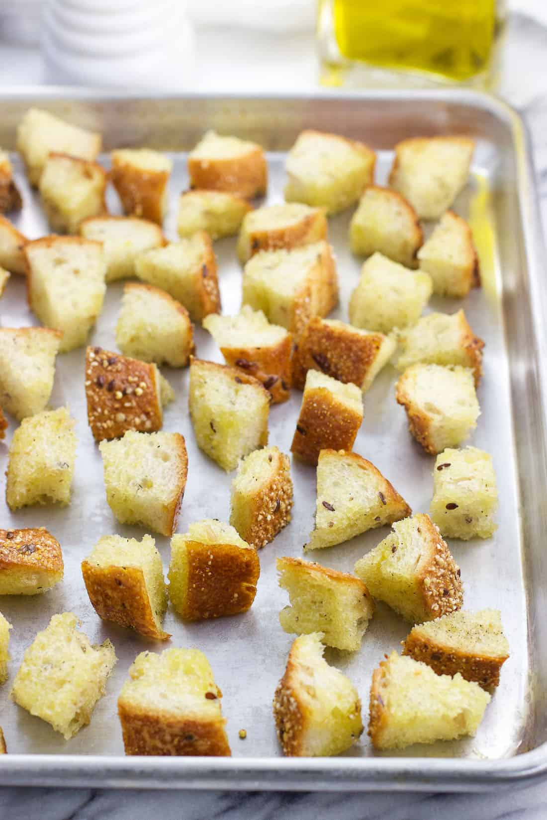 Croutons pre-bake on a steel rimmed baking sheet