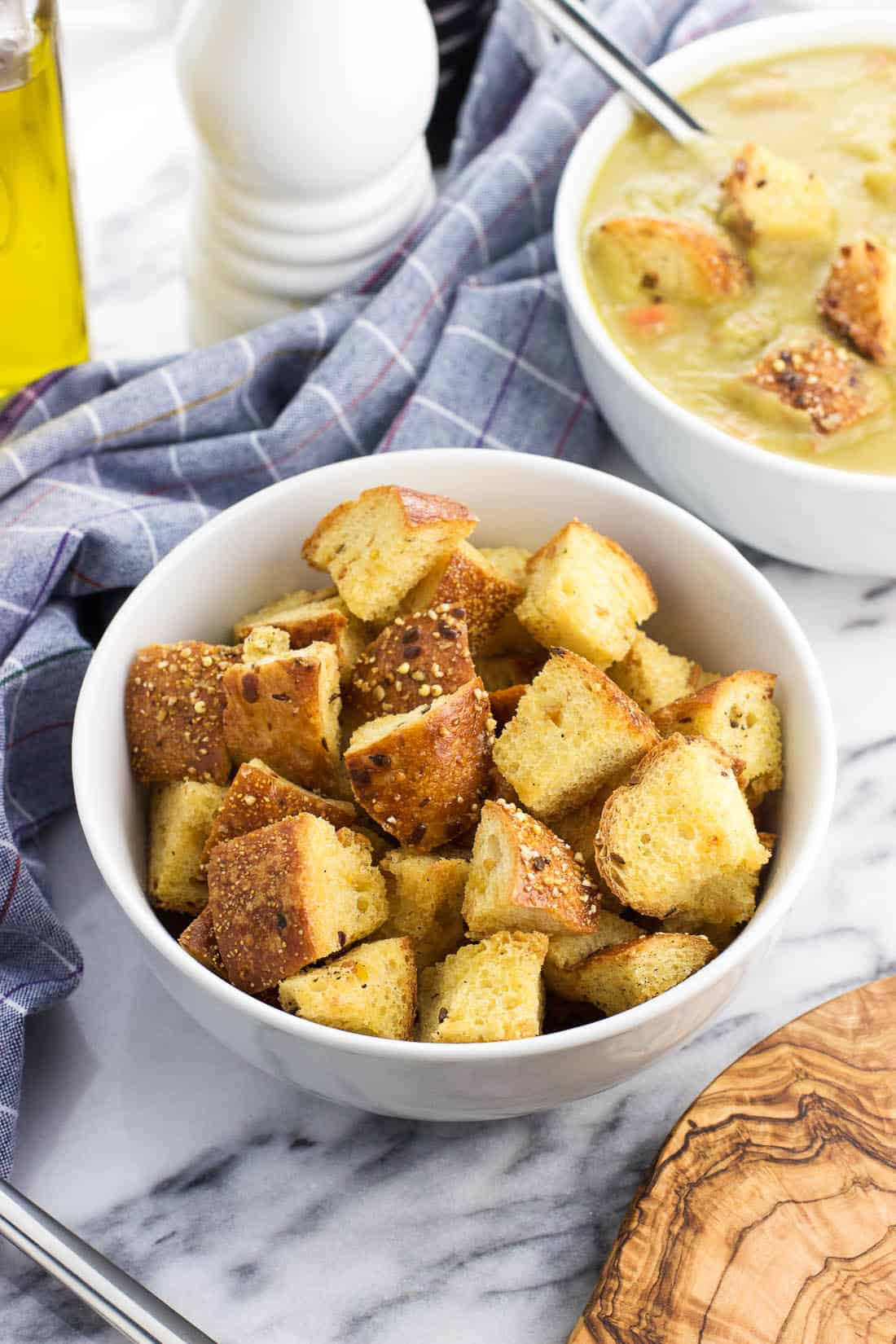 Homemade croutons in a bowl next to a bowl of soup
