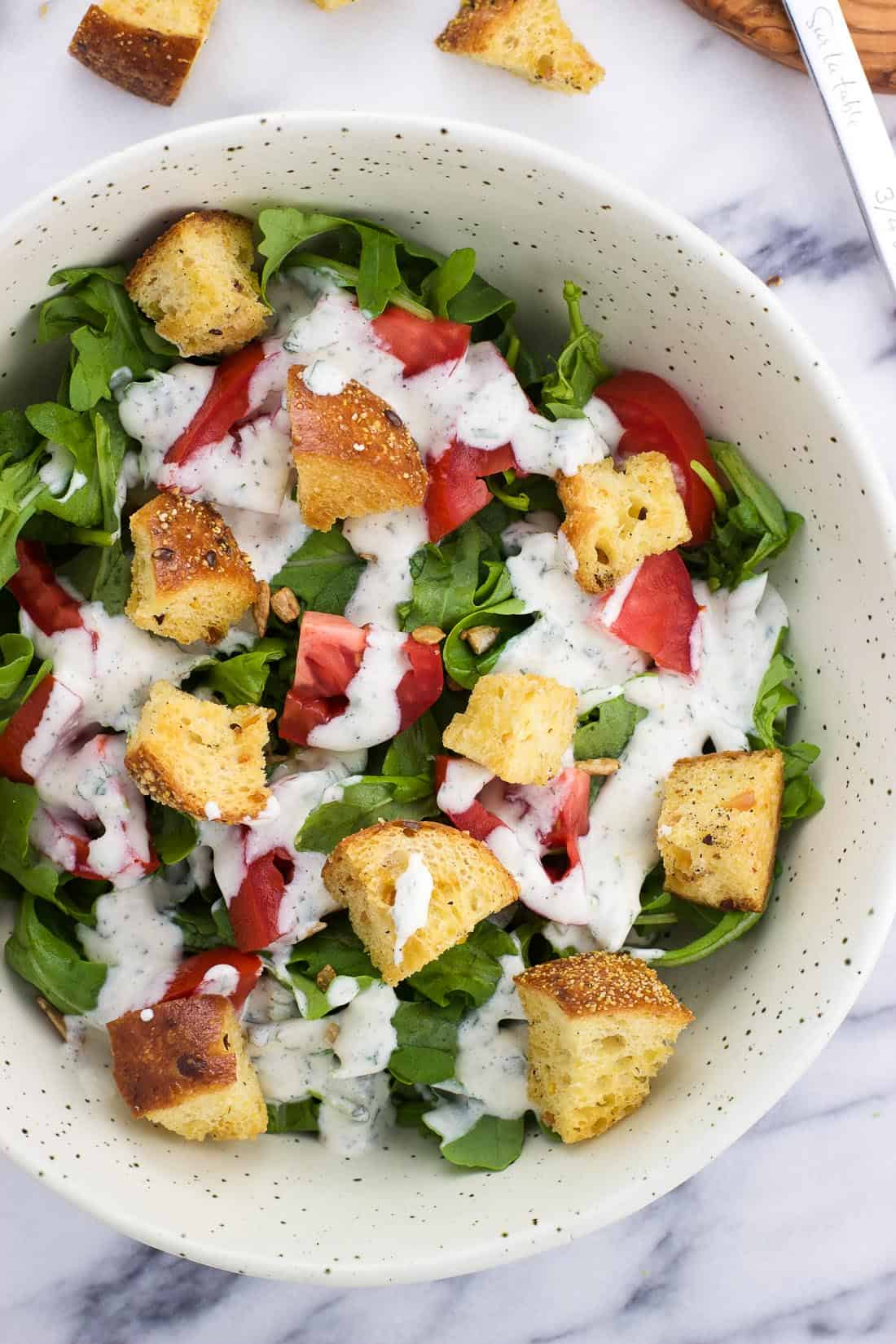 An overhead shot of homemade croutons in a salad with lettuce, tomatoes, and ranch salad dressing