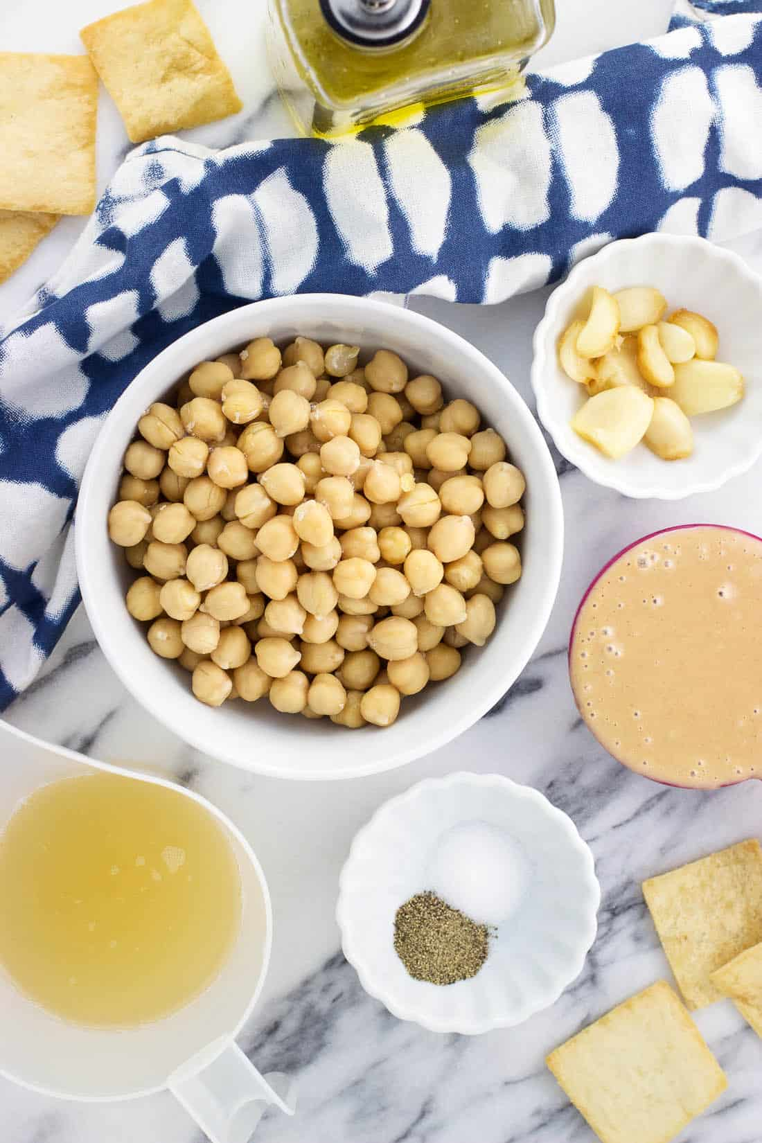 An overhead shot of chickpeas, tahini, roasted garlic cloves, olive oil, and spices