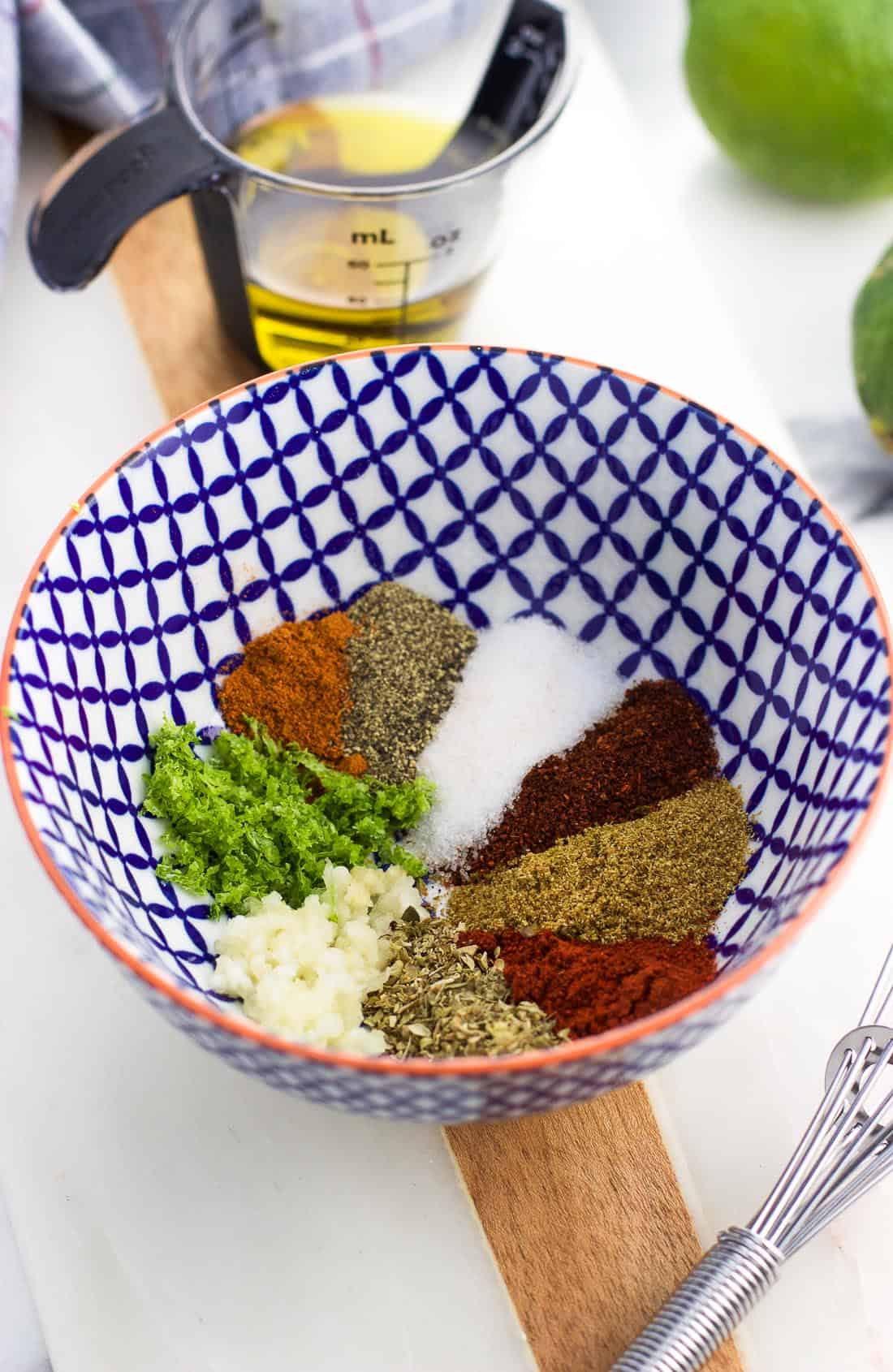 The dry spices, minced garlic, and lime zest used in the glaze in a small bowl