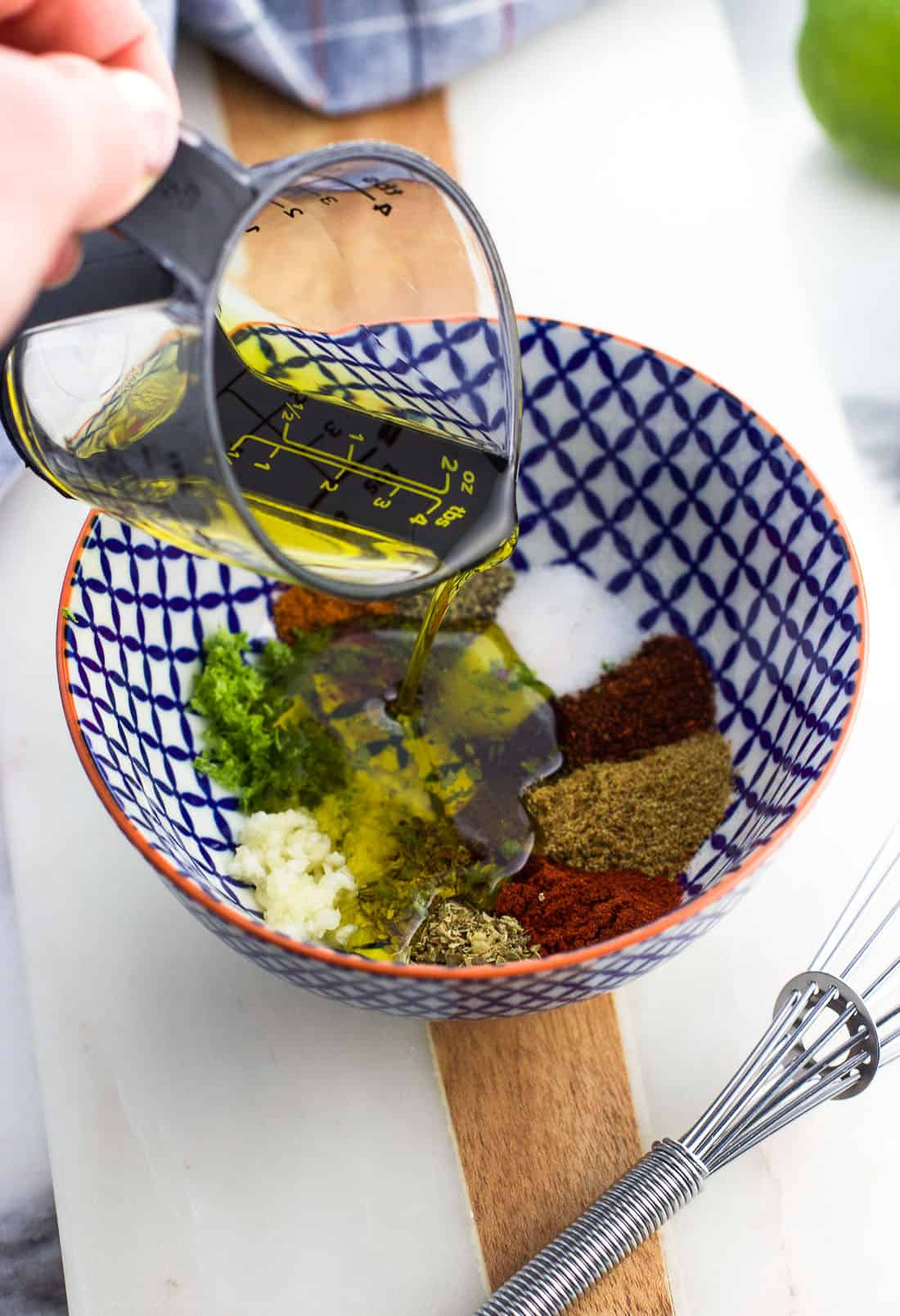 Olive oil being poured into the small bowl with the chili lime seasonings