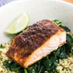 A cooked salmon fillet served on a bed of sauteed spinach over rice