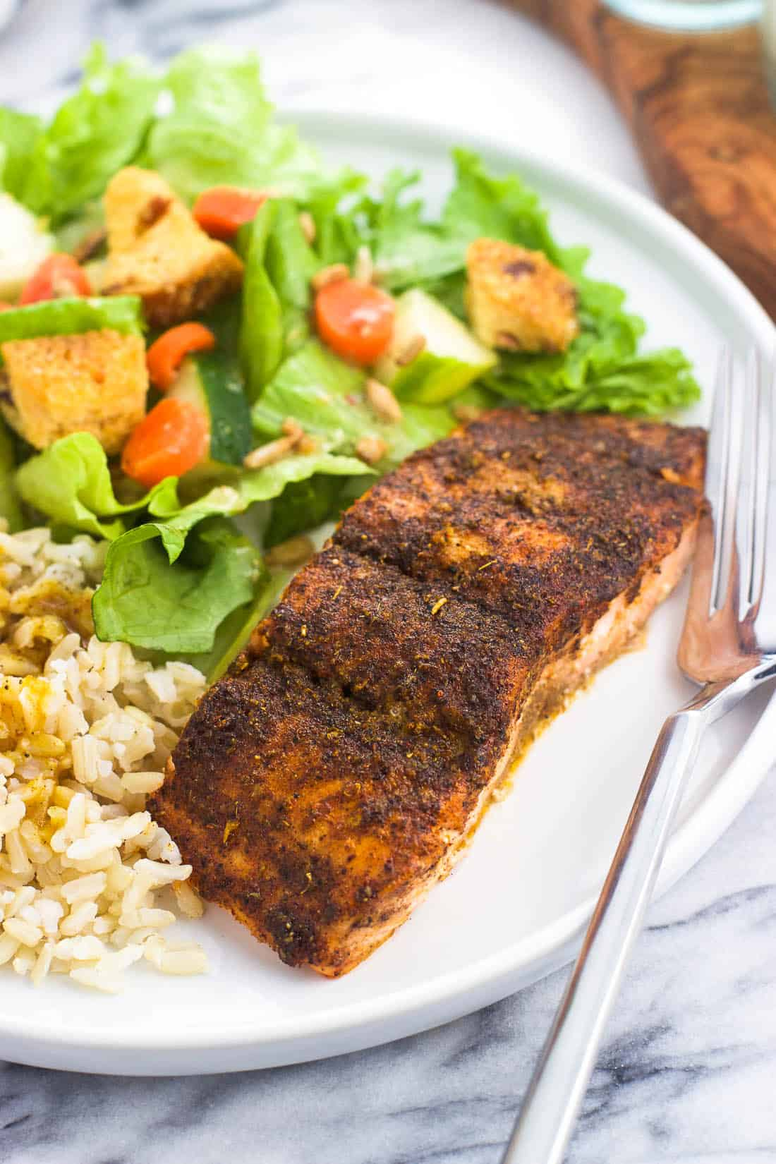 A plate of chili lime salmon, brown rice, and a side salad