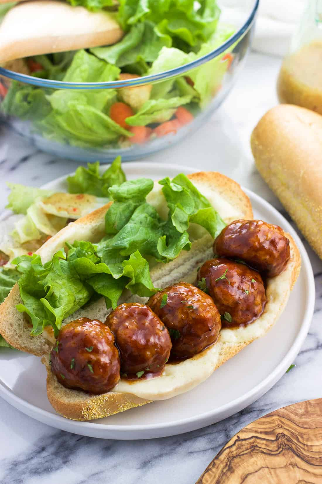 A baked honey BBQ chicken meatball sandwich with cheese and lettuce on a plate
