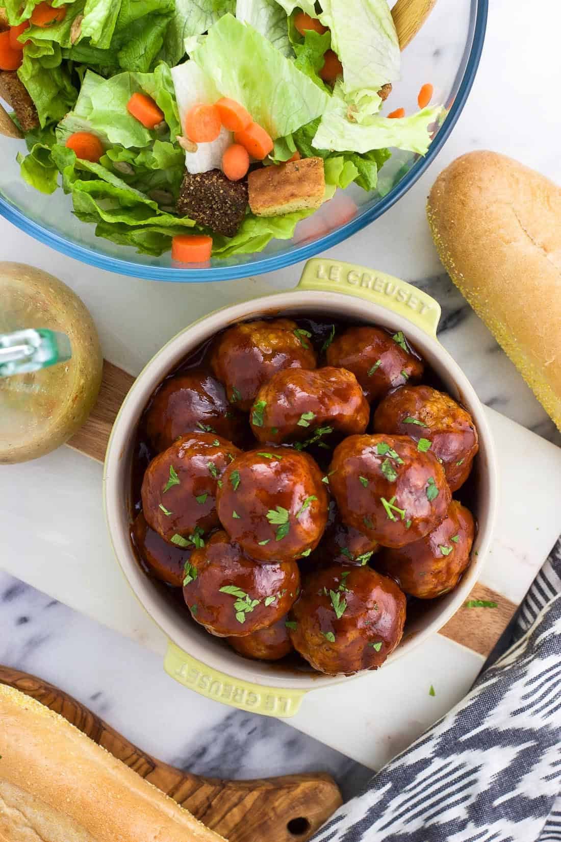 An overhead shot of glazed BBQ chicken meatballs in a bowl next to a bowl of salad and bread rolls