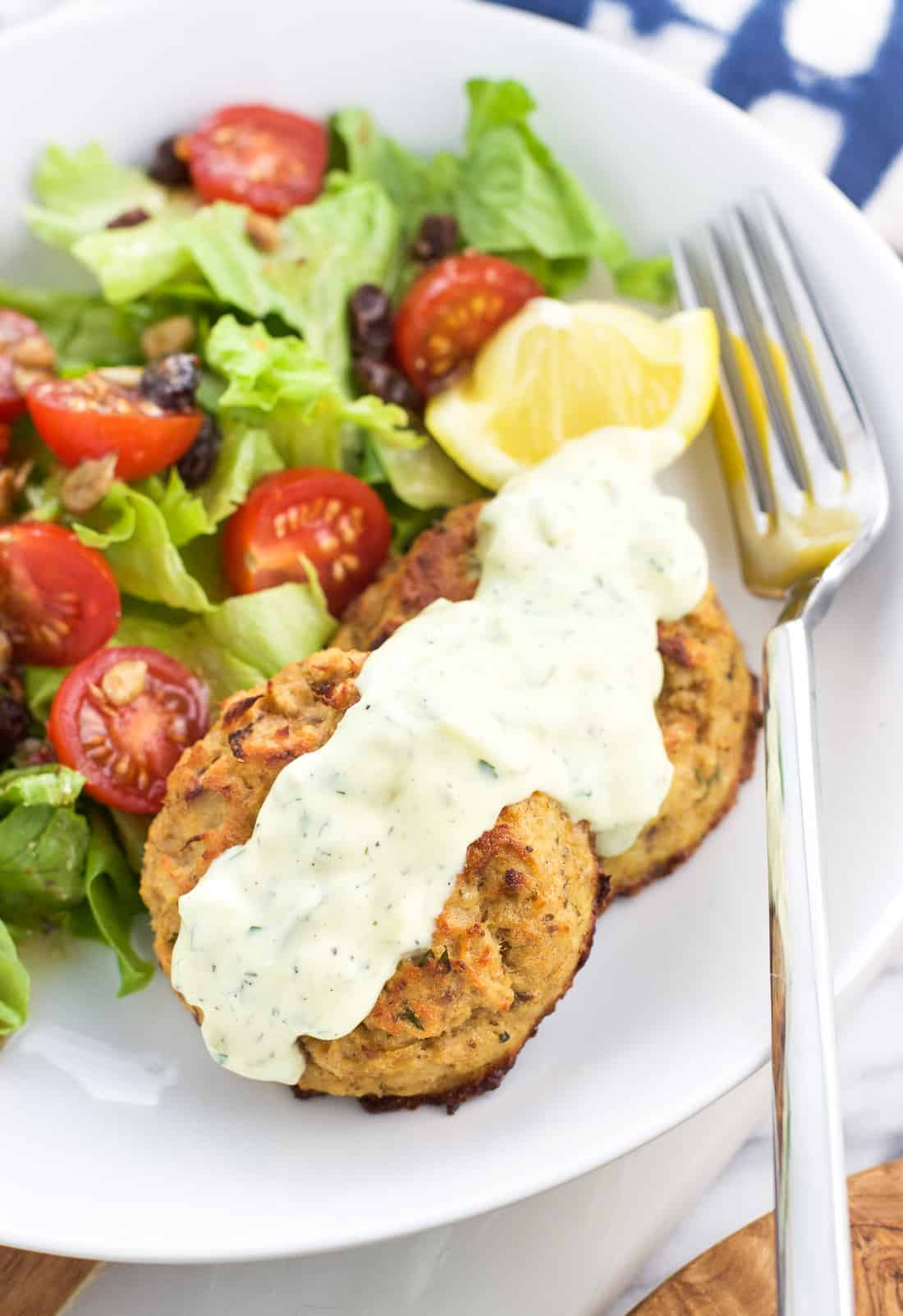 Two baked tuna cakes on a plate with a drizzle of tartar sauce, a lemon wedge, and a side salad