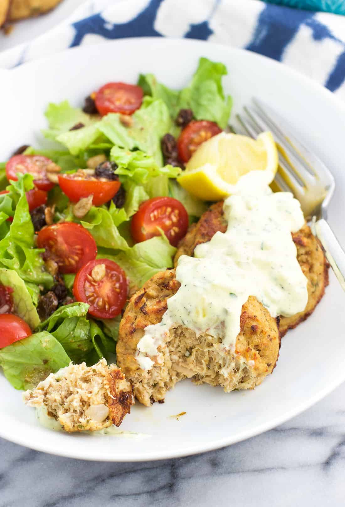 Healthy baked tuna cakes on a plate with a forkful removed from one of the cakes