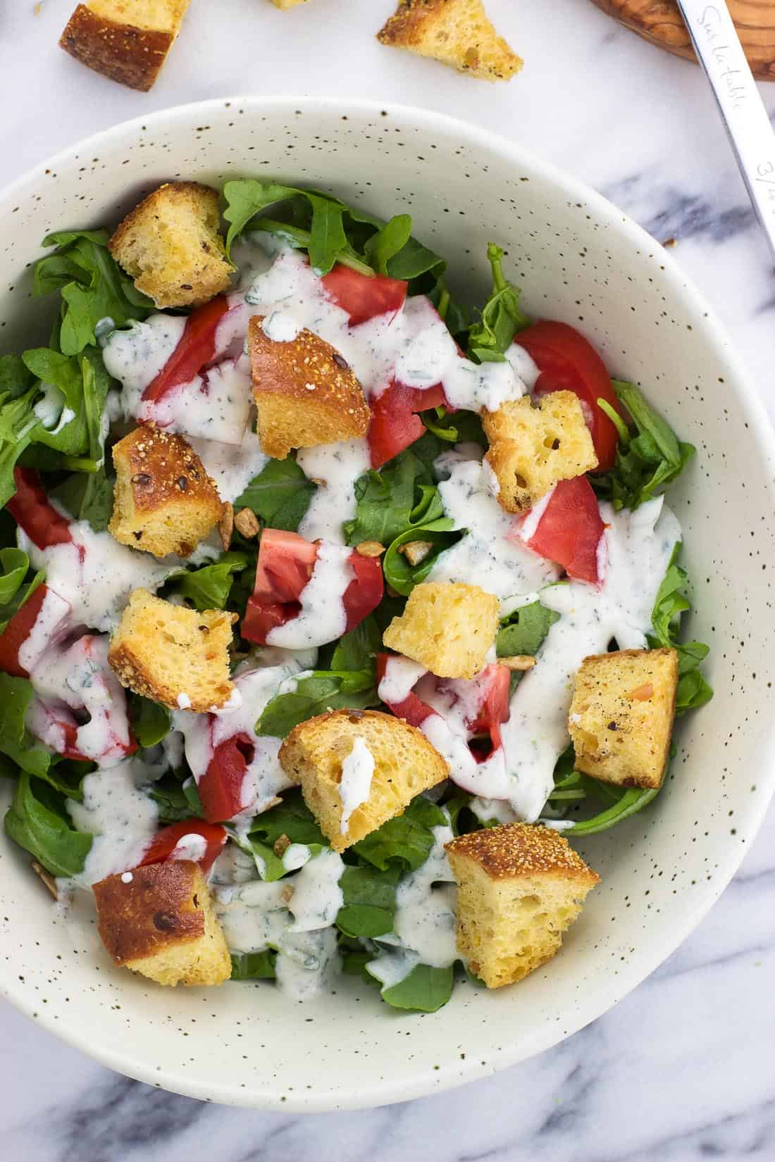 An overhead shot of a bowl of lettuce topped by chopped tomatoes, croutons, and cilantro lime ranch