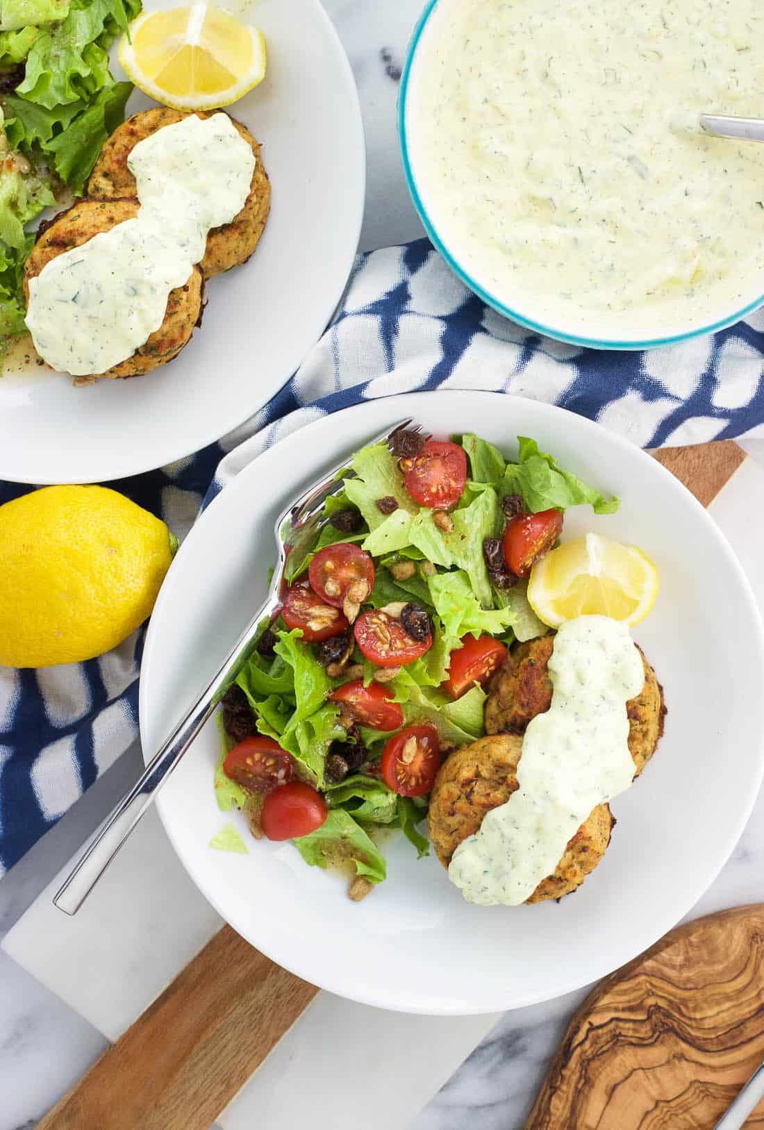 An overhead shot of a plate of two tuna cakes, a drizzle of tartar sauce, a lemon wedge, and a side salad