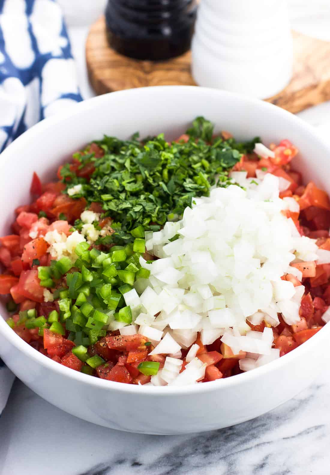 All pico de gallo ingredients in a bowl ready to be mixed together.