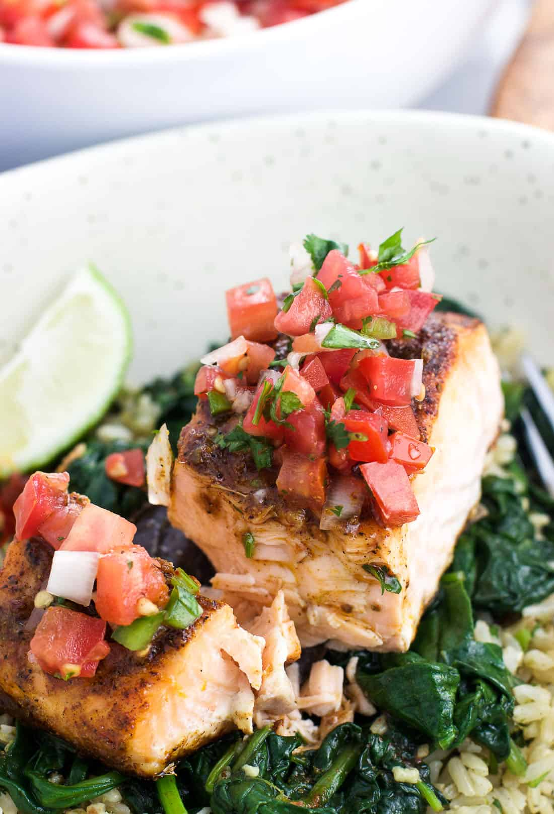 Pico de gallo on top of a baked salmon fillet on a bed of spinach and rice in a bowl.