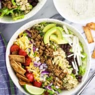 An overhead shot of quinoa turkey taco salad in a bowl with the toppings arranged in strips on top of the lettuce