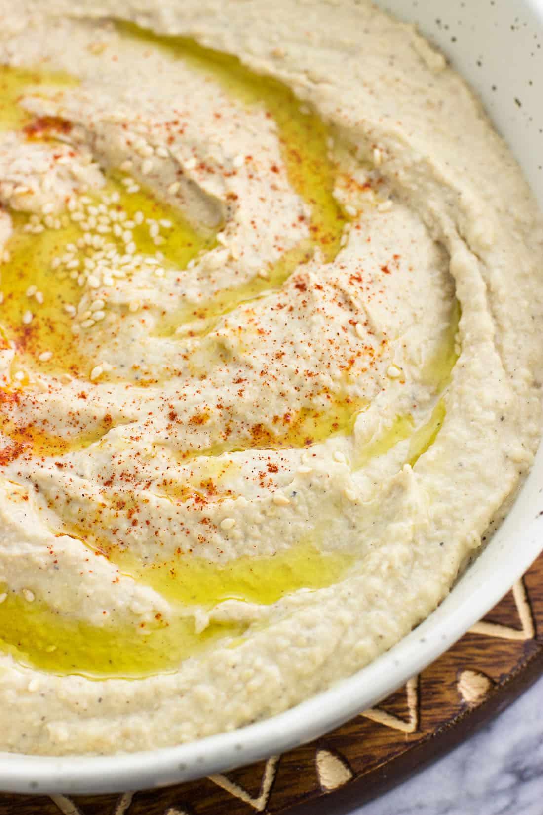 A close-up shot of roasted garlic hummus in a bowl