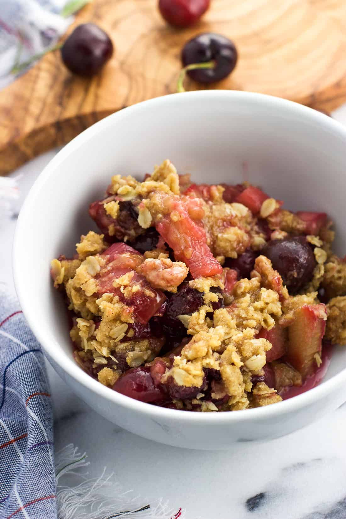 A serving of cherry rhubarb crisp in a bowl