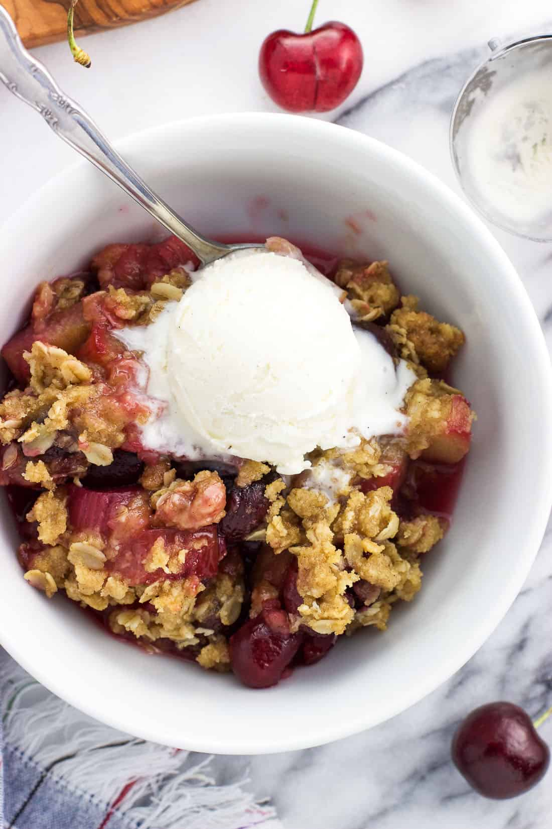 An overhead shot of a serving of fruit crisp in a bowl with a spoon and a scoop of vanilla ice cream