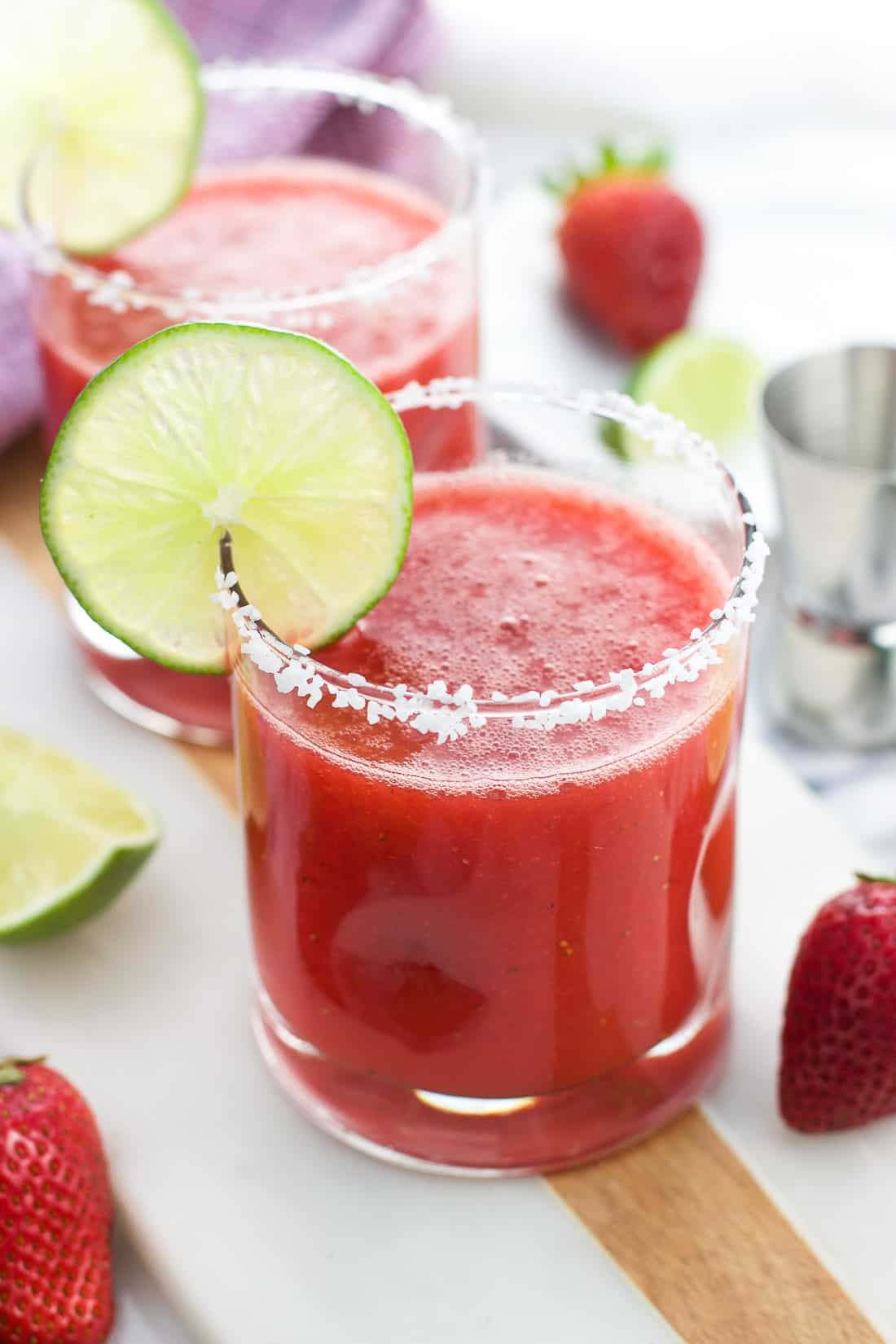 A strawberry ginger margarita in a glass with a salted rim and a lime round as garnish