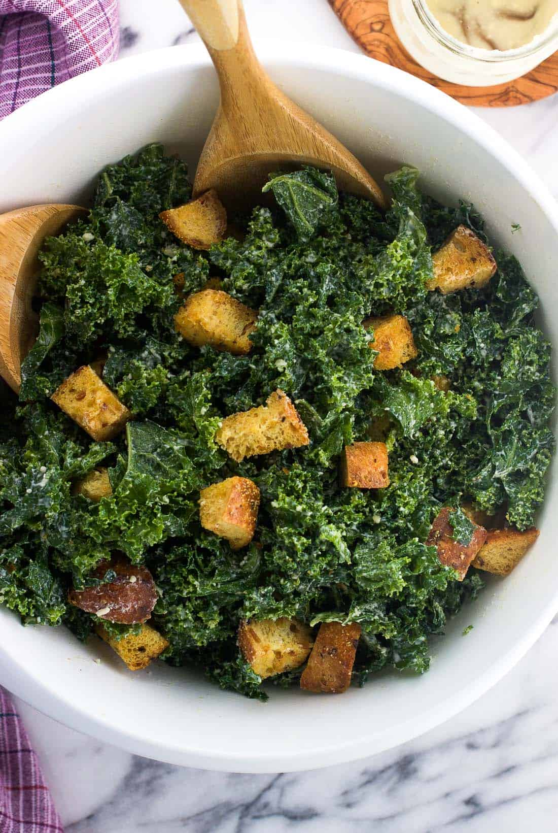 Massaged kale caesar salad in a big mixing bowl with croutons and salad tongs
