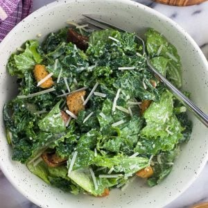 An overhead shot of kale caesar salad in a bowl with a fork