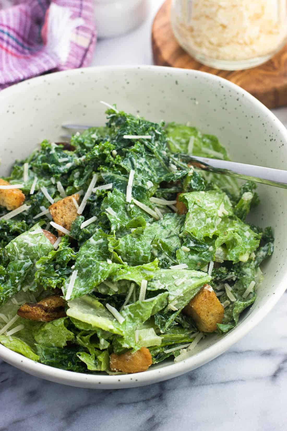 Greek yogurt kale caesar salad in a bowl with a fork