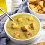 A bowl of split pea soup topped with croutons with a spoon