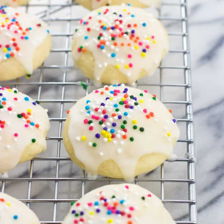 Iced and sprinkled Italian ricotta cookies on a wire rack
