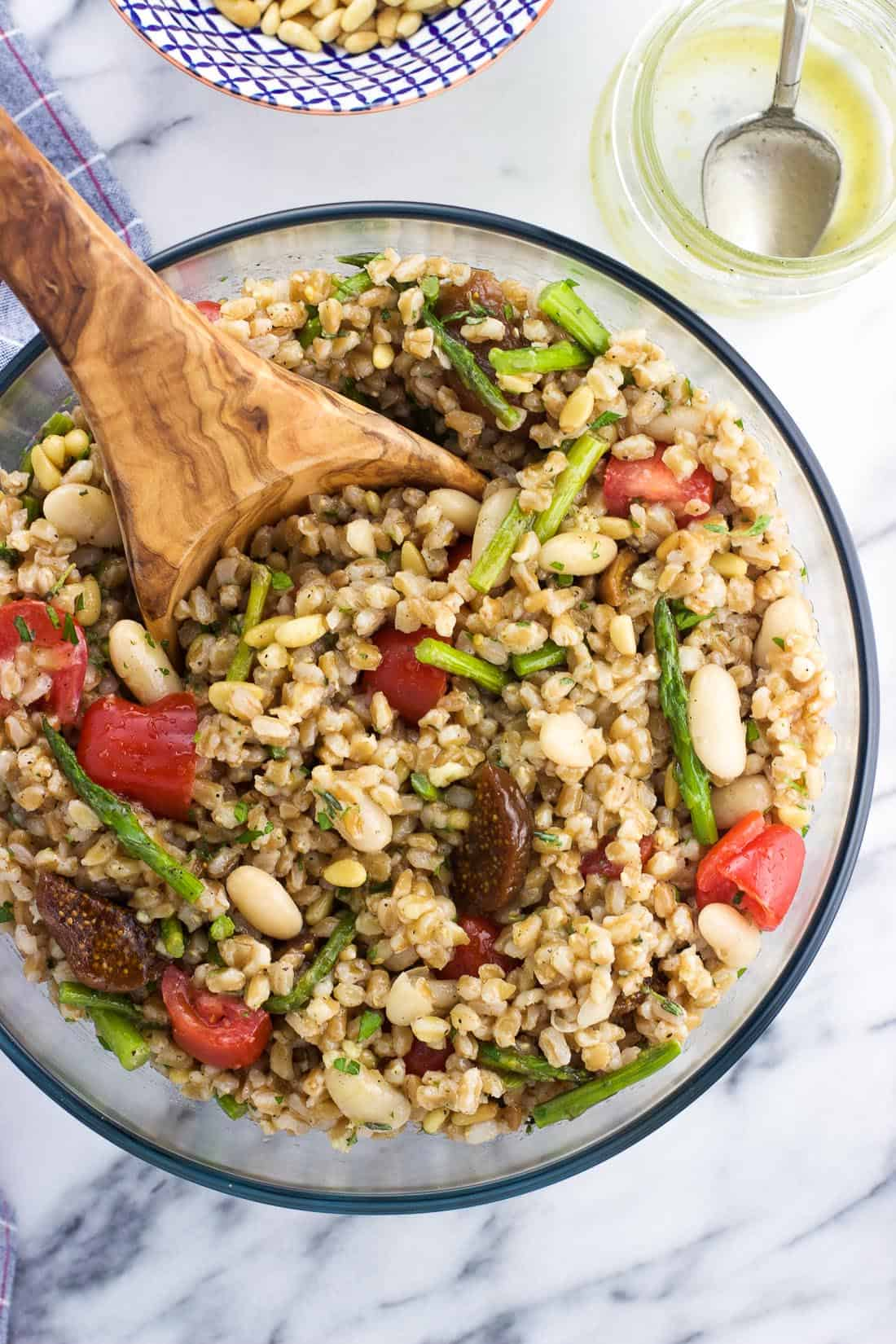 An overhead shot of Mediterranean farro salad in a serving bowl with a wooden serving spoon
