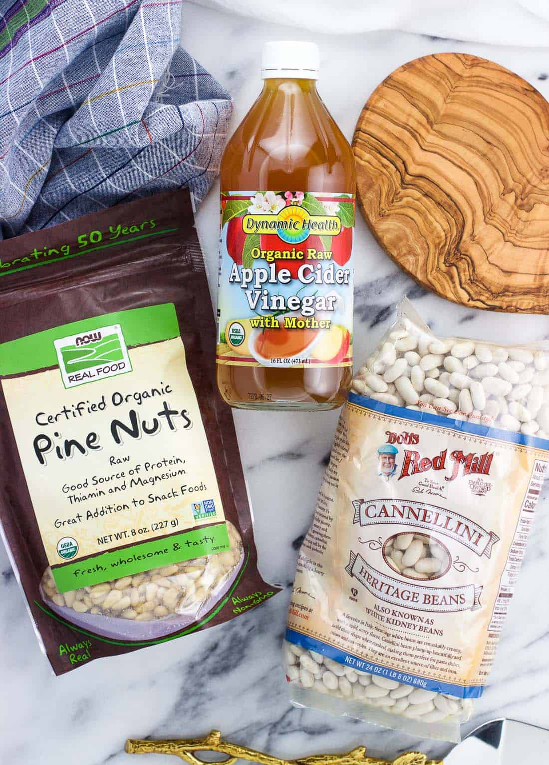 An overhead shot of ingredients from iHerb: pine nuts, apple cider vinegar, and cannellini beans