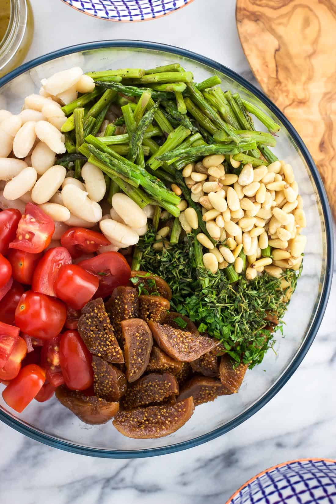 An overhead shot of tomatoes, white beans, asparagus, pine nuts, herbs, and figs on top of farro in a serving bowl before being mixed together.