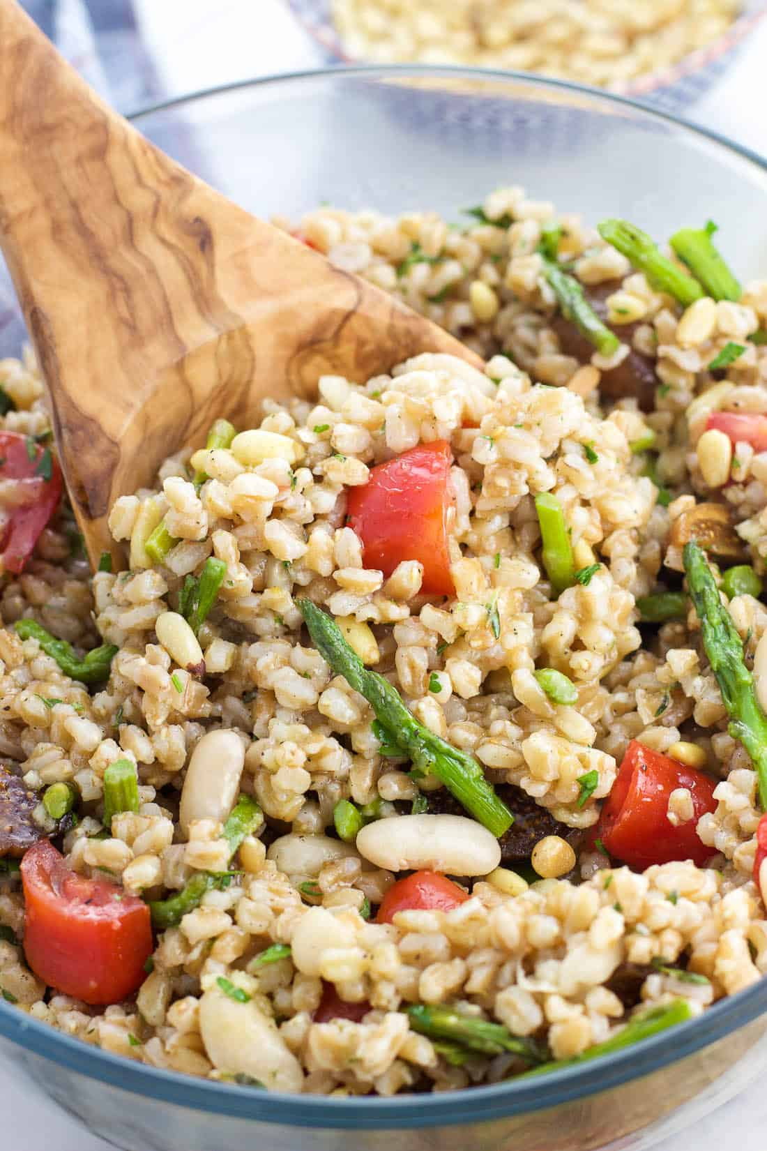 A wooden serving spoon scooping out a portion of farro salad from a serving bowl