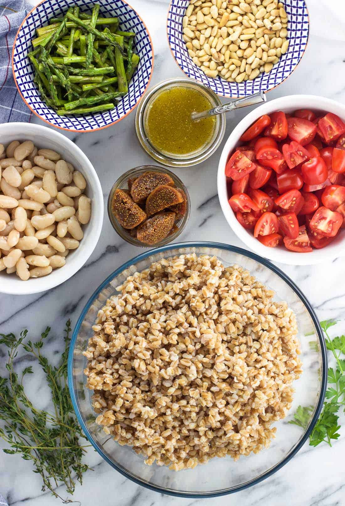 An overhead shot of the ingredients in separate bowls: cooked farro, white beans, figs, dressing, asparagus, and tomatoes with fresh herbs