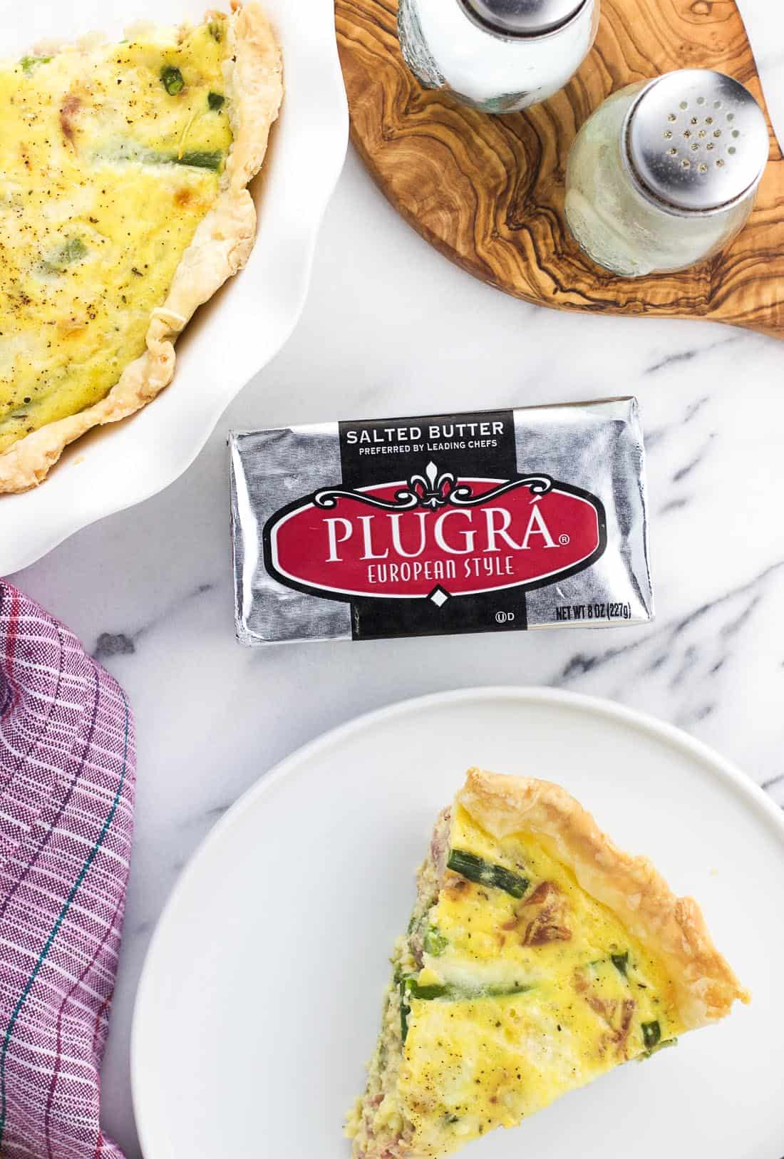 A package of Plugra butter on a marble board surrounded by a slice of quiche on a plate and the rest of the quiche in a pie plate