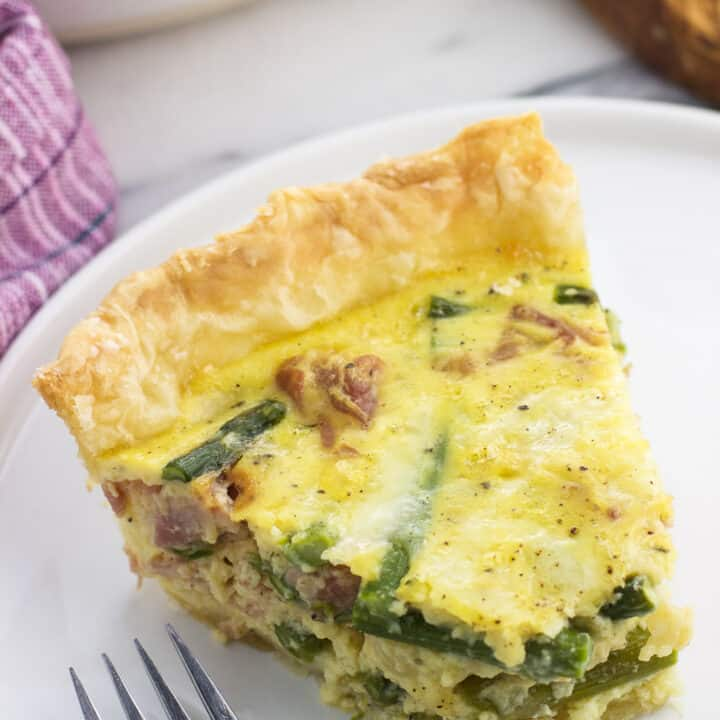 A slice of quiche on a plate with a bite taken out next to a fork