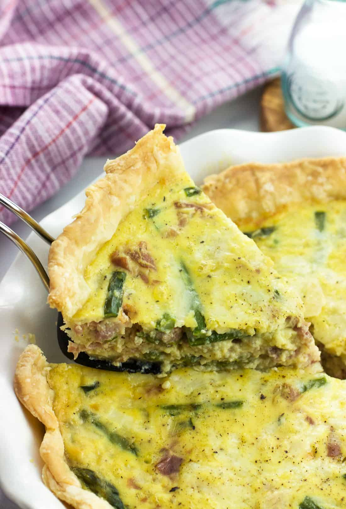 A slice of quiche being lifted out of the pie plate with a wedge-shaped spatula