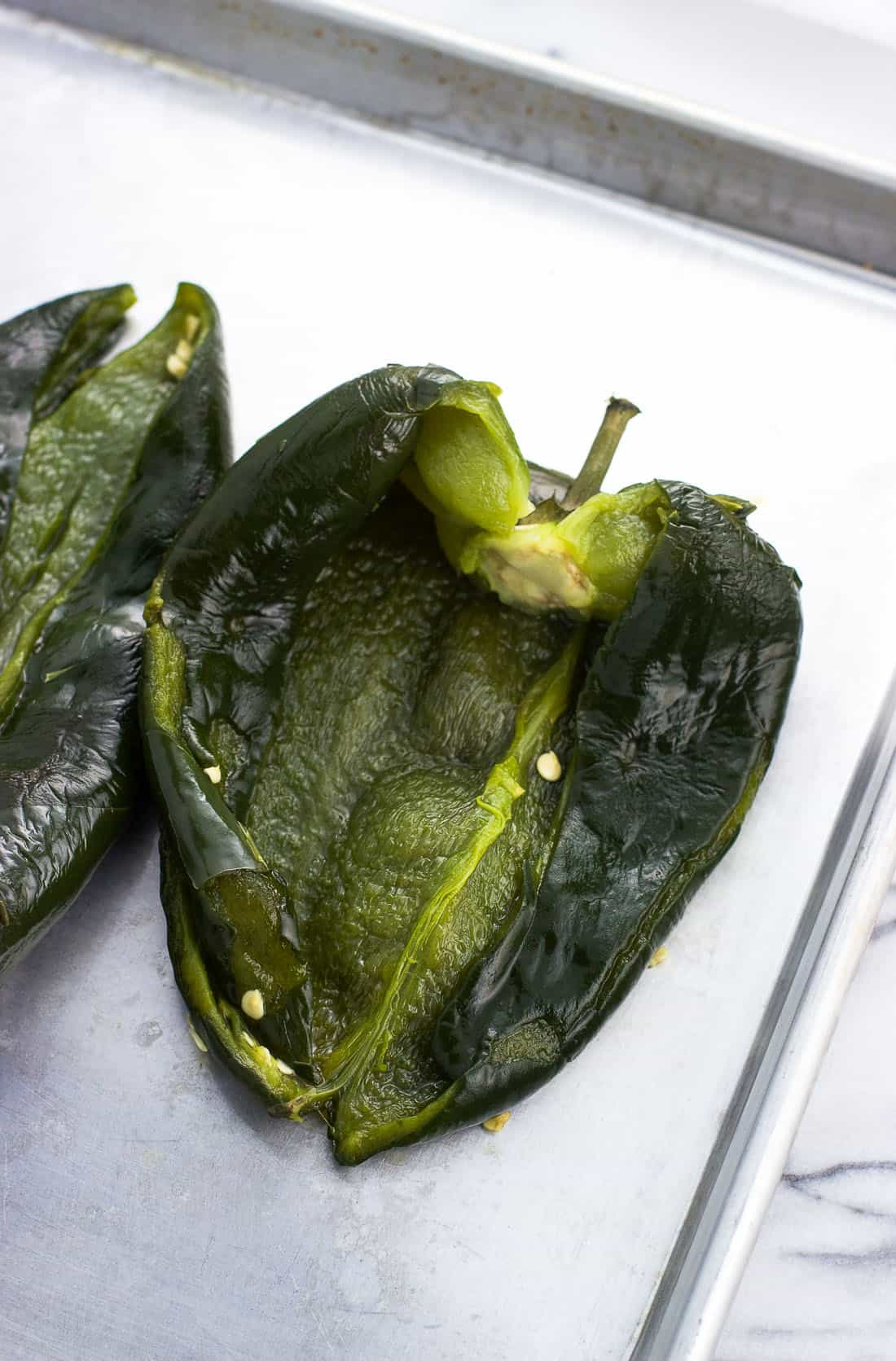 A roasted poblano pepper on a metal baking sheet split open