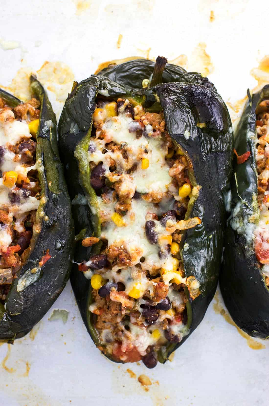 An overhead shot of roasted and stuffed poblano peppers on a metal baking sheet