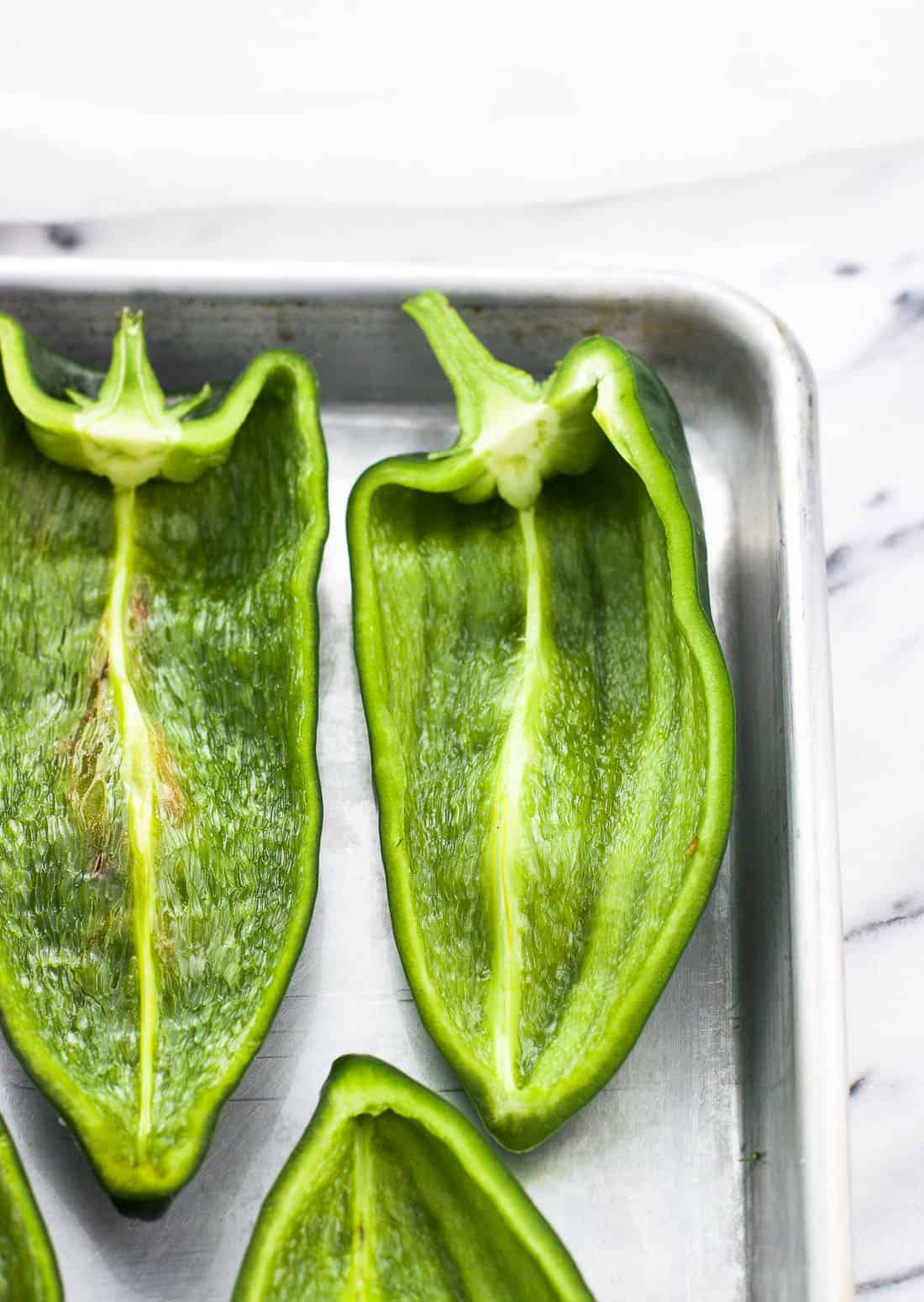 Raw poblano peppers halved and lined up next to one another on a metal baking sheet
