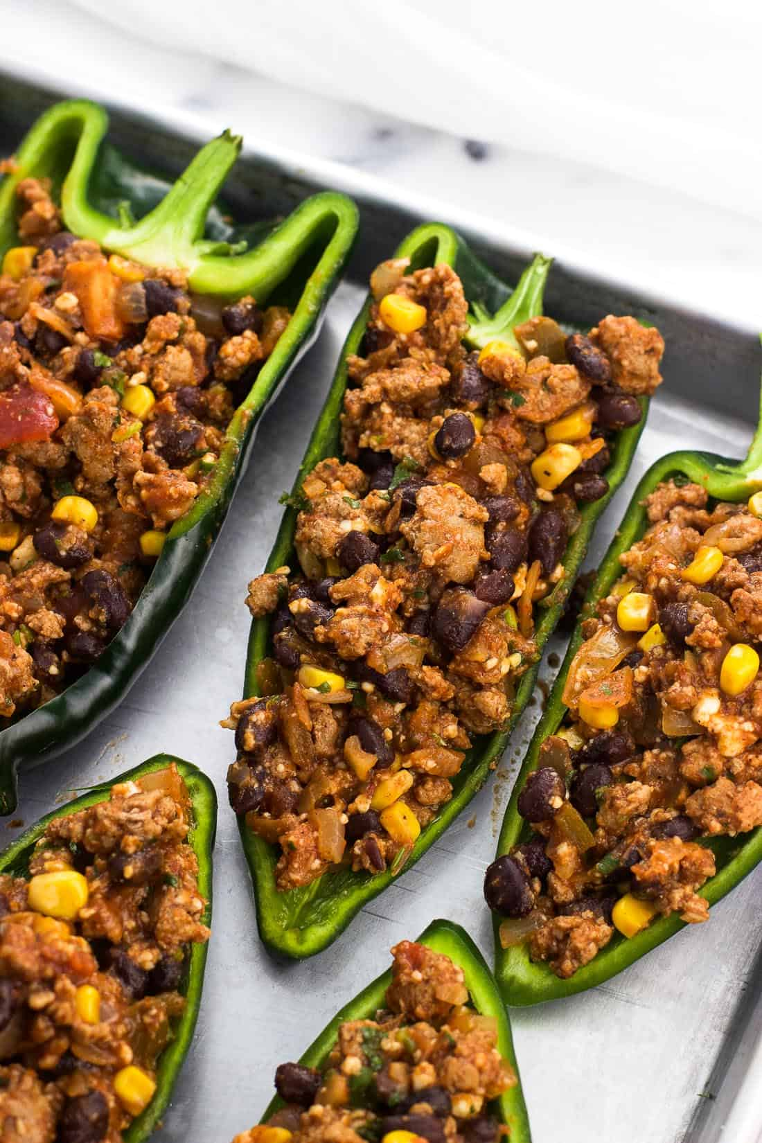 Stuffed poblano peppers on a metal baking sheet before being topped with cheese