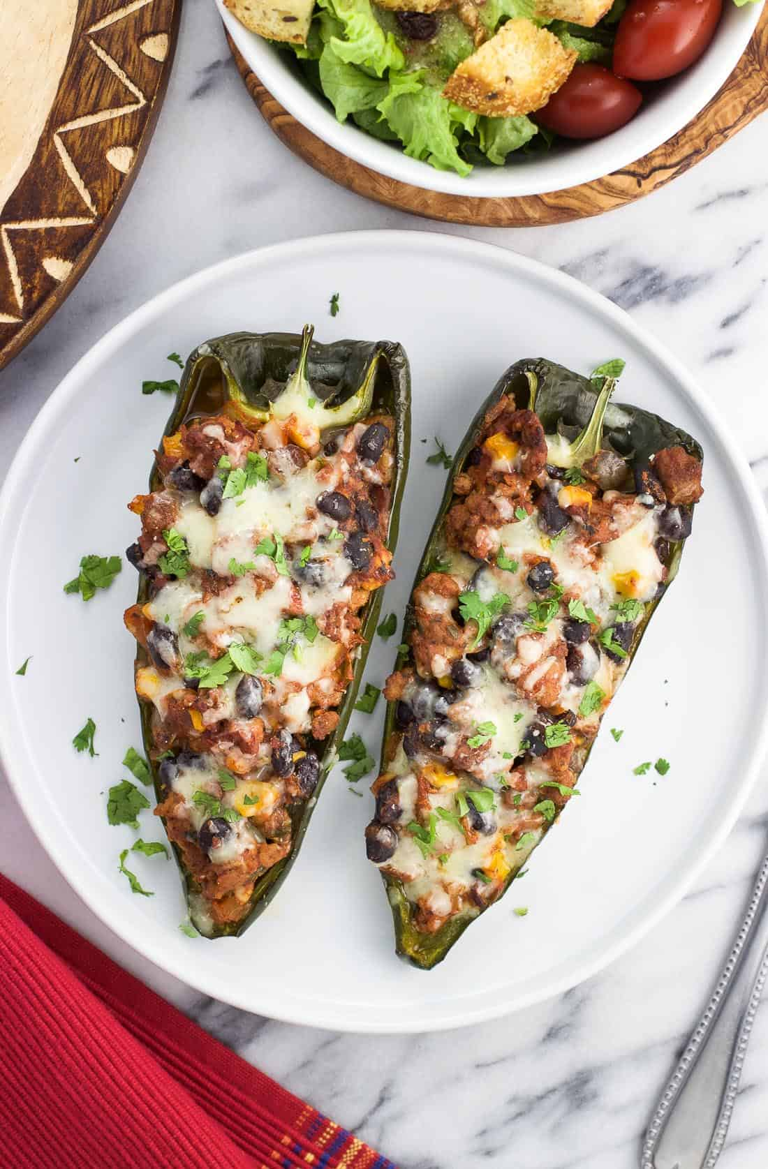 Two stuffed poblano pepper halves on a plate
