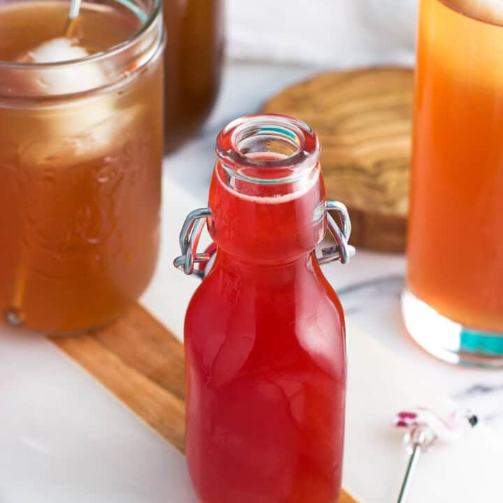 A small glass jar of strawberry syrup with glasses of iced tea in the background