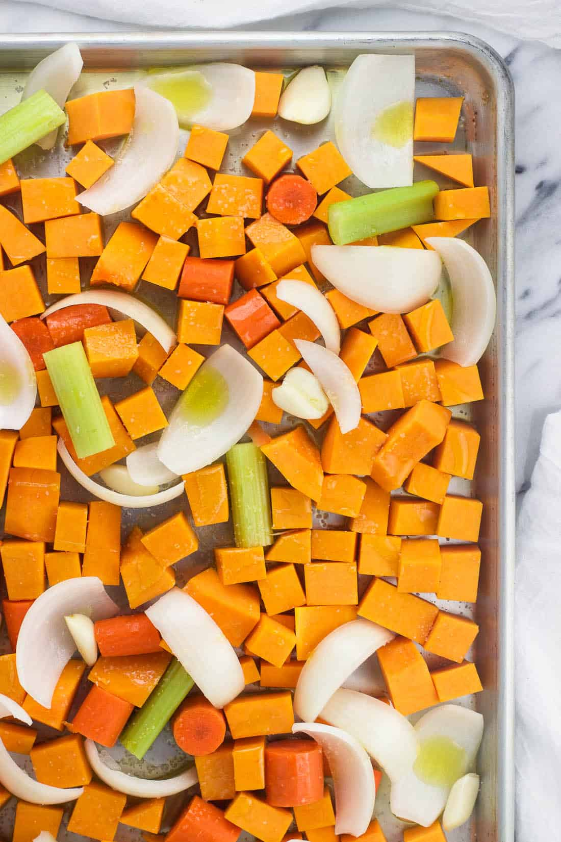 Butternut squash soup ingredients on a baking sheet before roasting, including butternut squash cubes, carrots, celery, onion, and garlic cloves