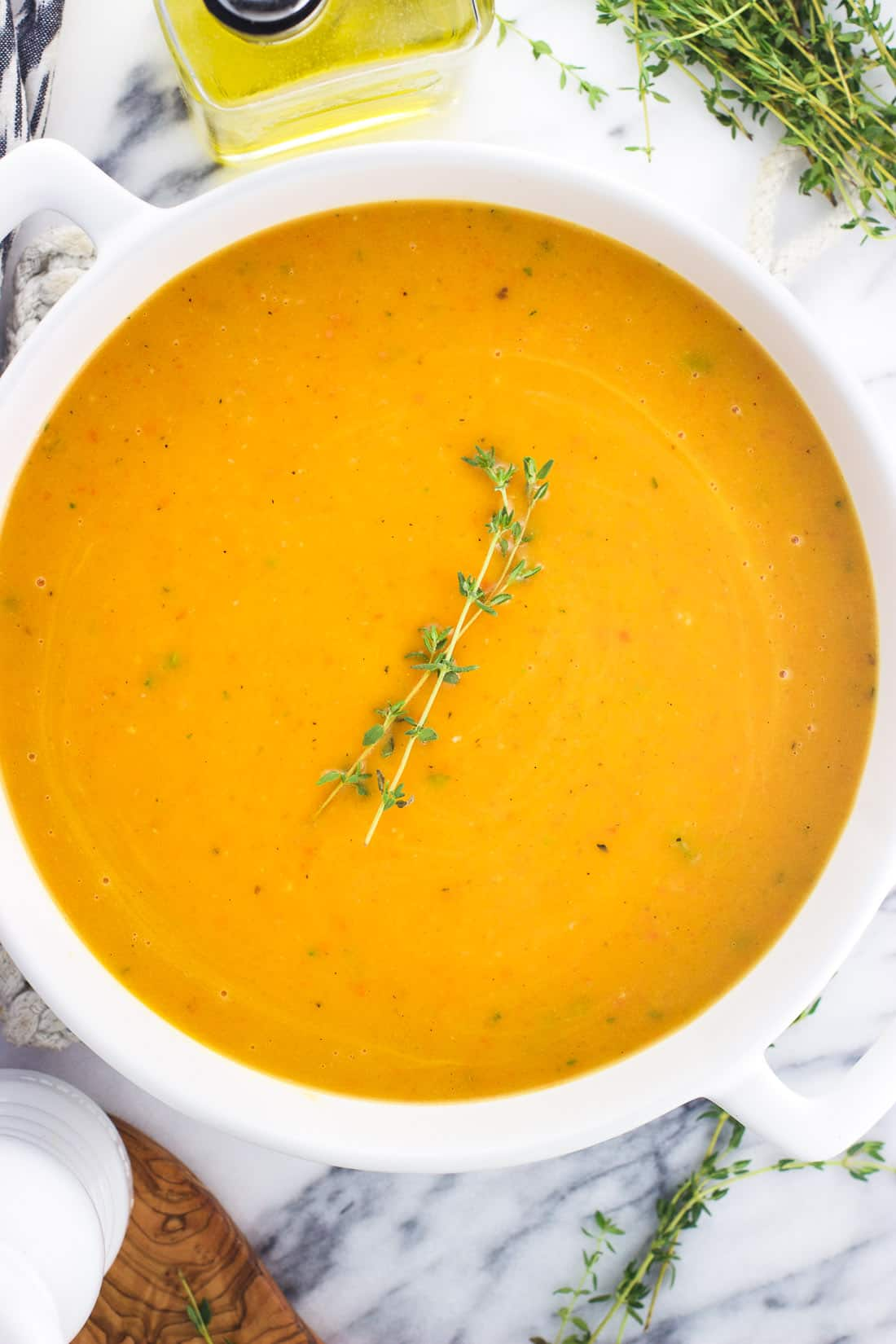Butternut squash soup in a large soup pot topped with thyme sprigs
