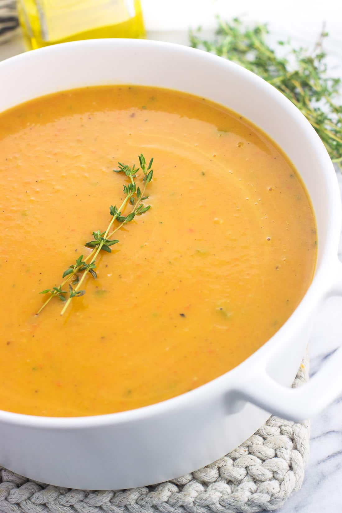 Butternut squash soup in a soup pot garnished with a sprig of thyme