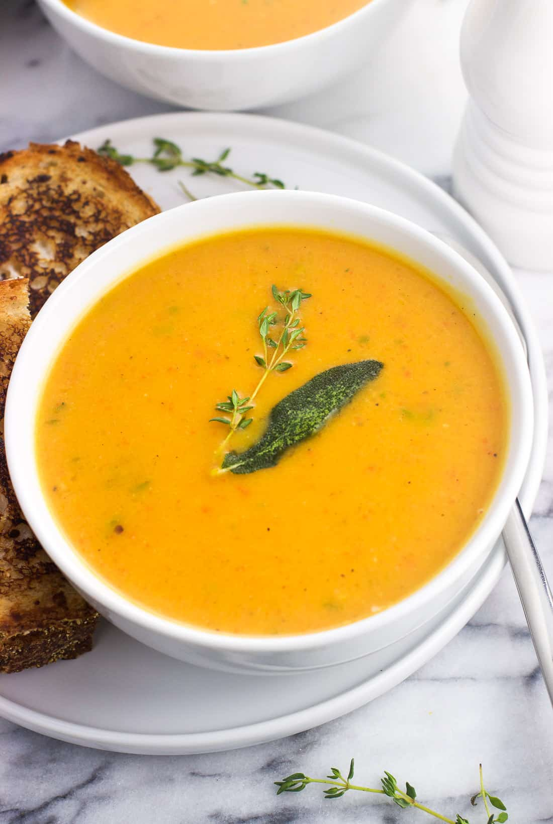 A bowl of roasted butternut squash soup garnished with a sprig of thyme and a sage leaf, served next to a grilled cheese sandwich