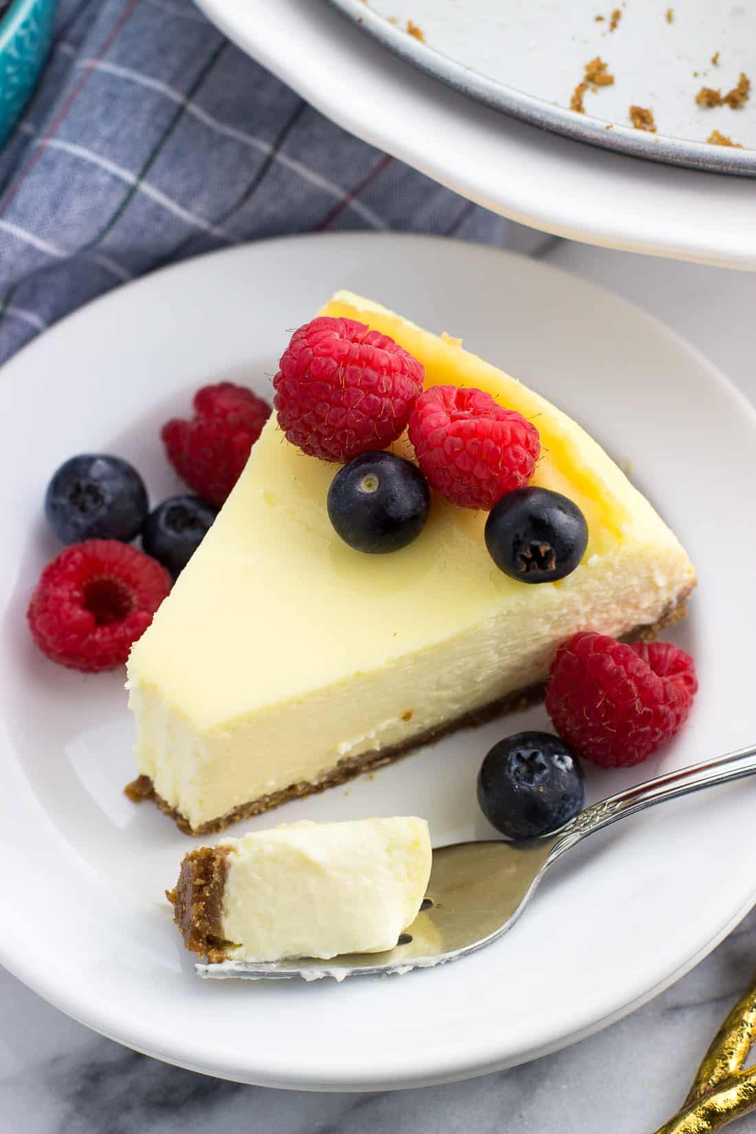 A slice of cheesecake on dessert plate topped with mixed berries