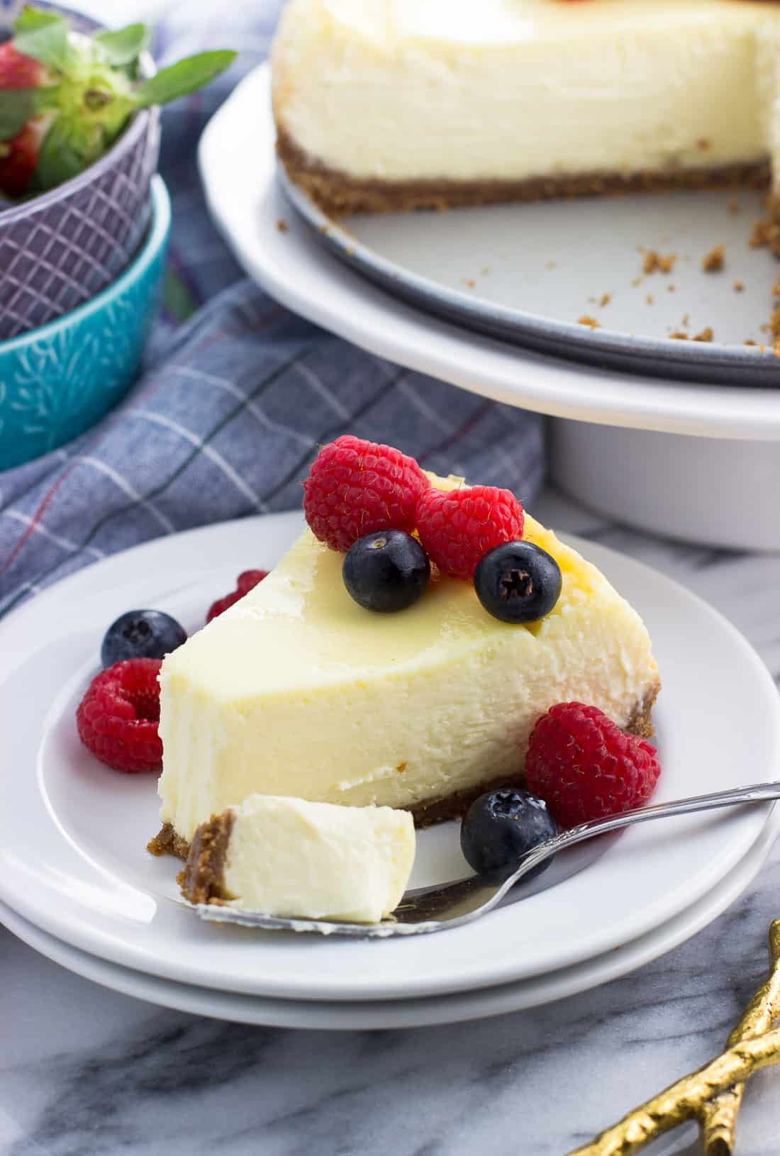 A slice of sour cream cheesecake on a dessert plate with a forkful taken out