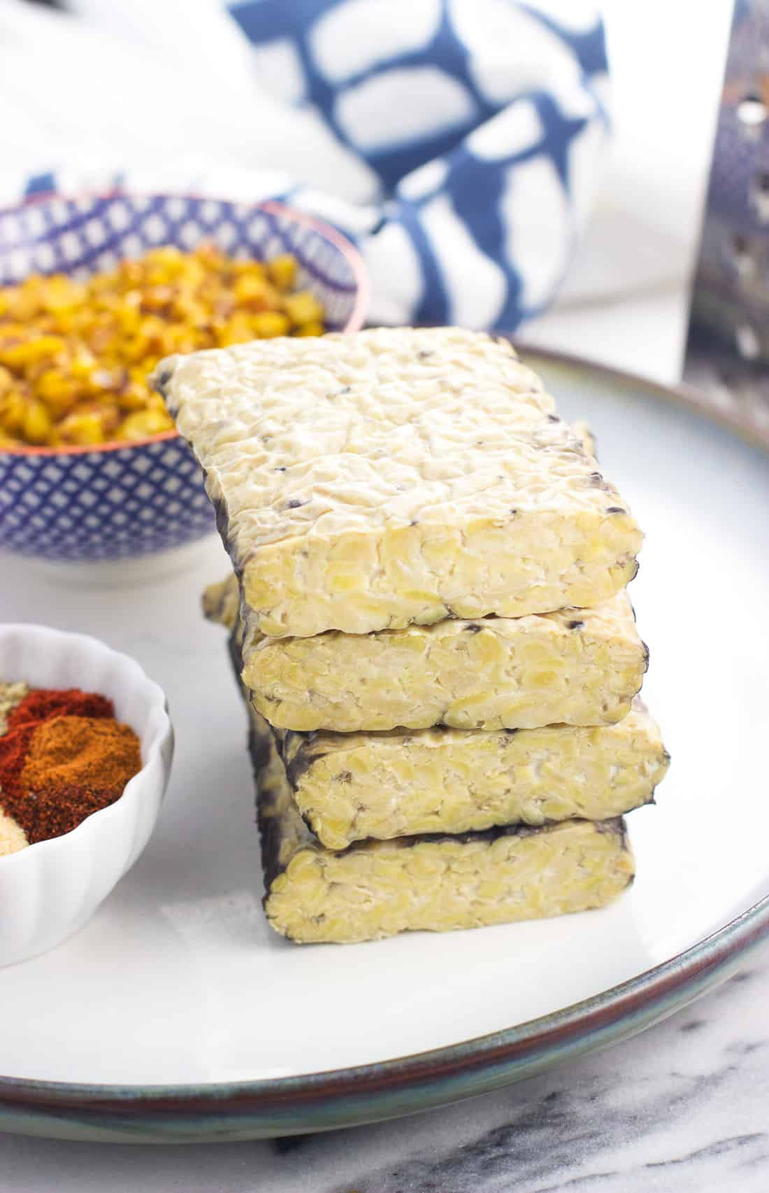 Blocks of tempeh stacked on top of one another on a ceramic plate next to taco seasoning and roasted corn